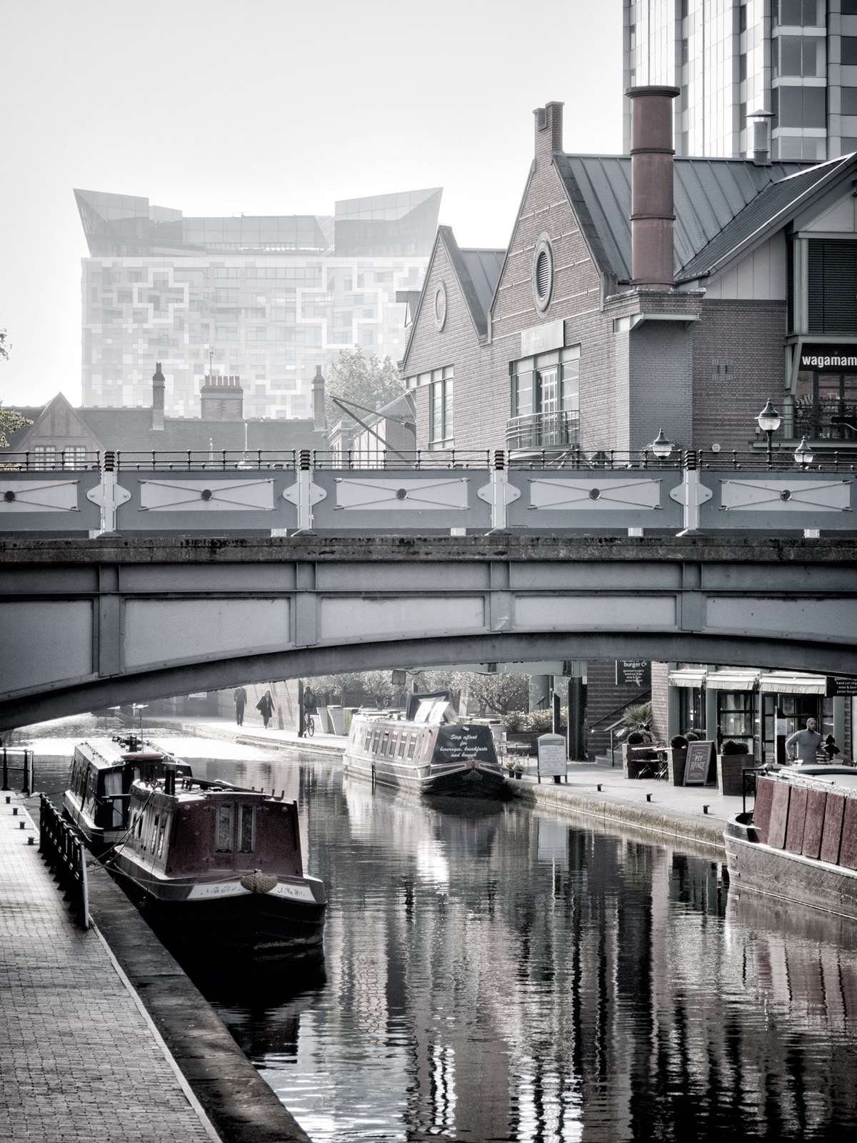 Looking along Brindley Place in Birmingham towards 'The Cube' with Brewmaster's Bridge in the foreground.